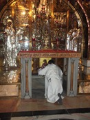 Thomas kneeling at the altar above the stone of Golgotha