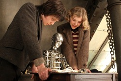 Hugo and Isabelle watch as Melies' automaton draws a magical image.