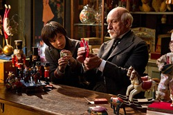 Hugo and Melies work to repair a small toy. Their mentoring relationship is the heart of the film.